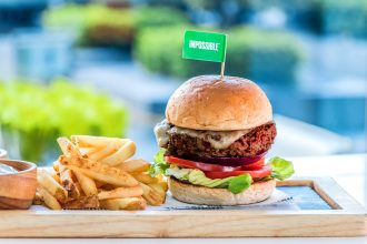 Impossible Burger on a plate with fries.