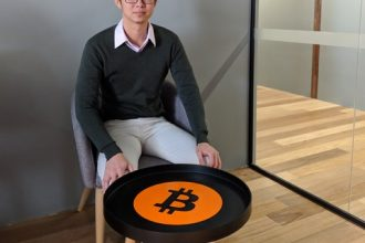 Caleb Yeoh sitting behind a bitcoin branded table.
