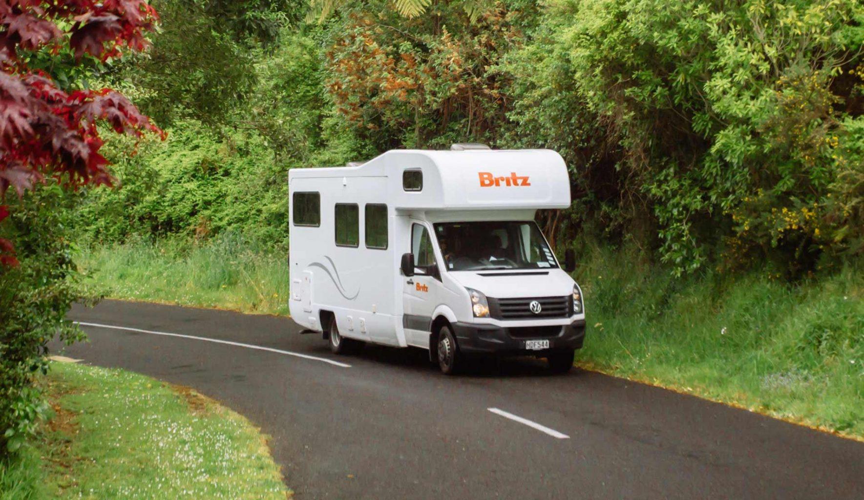 Britz rental campervan drives down a rural road.