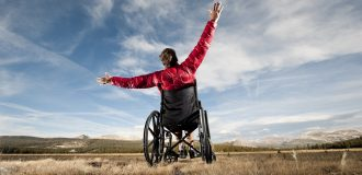 Man in wheelchair raises hands to the sky.