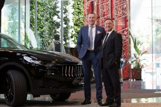 General manager and Maserati Brisbane sales manager stand in front of a Maserati Levante SUV.