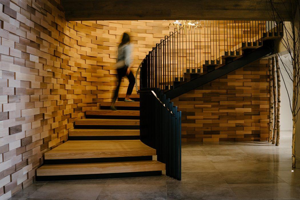 Guest walks up staircase at Kamana Lakehouse.