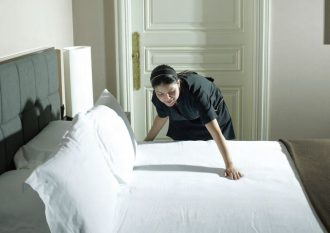 Housekeeping staff make bed with fresh laundry.