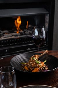 Red wine and lamb shank meal in front of fireplace